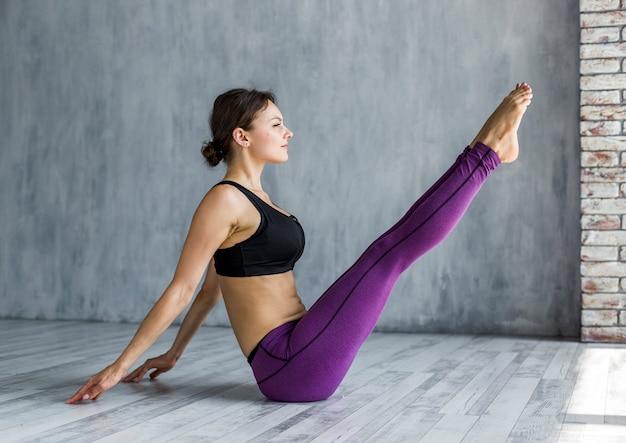 Donna che esegue una posa della barca di yoga