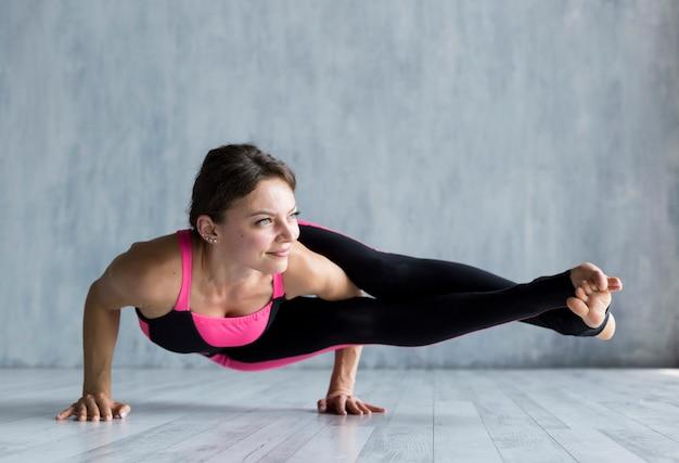 Donna che esegue una posa di yoga del corvo laterale