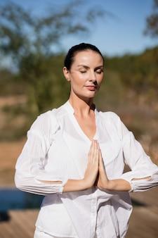 Donna che esegue yoga in vacanza safari