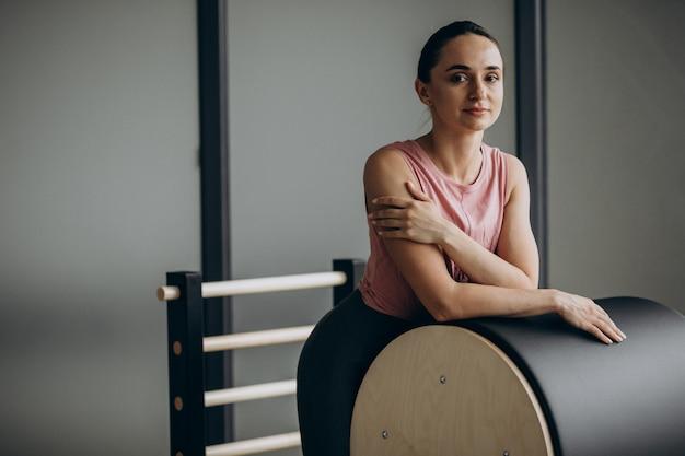 Donna che esercita i pilates sul riformatore