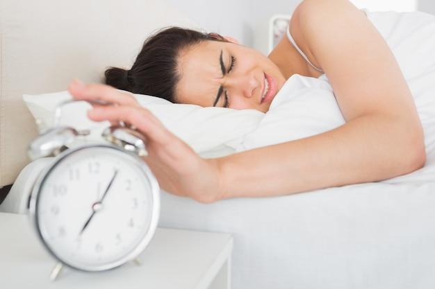 Donna che estende la mano alla sveglia a letto