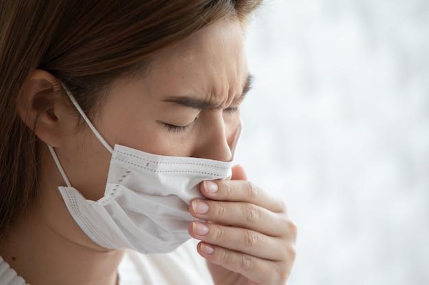 Donna che fa attenzione alla maschera di protezione dal coronavirus e dall'inquinamento atmosferico che tossisce così malattia, concetto di sanità