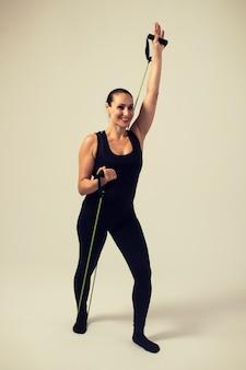 Donna che fa bicipiti e tricipiti con fitness elastico