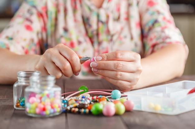Donna che fa bigiotteria di arte artigianale domestica