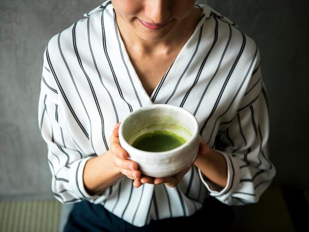 Donna che fa cerimonia giapponese del tè verde orientale