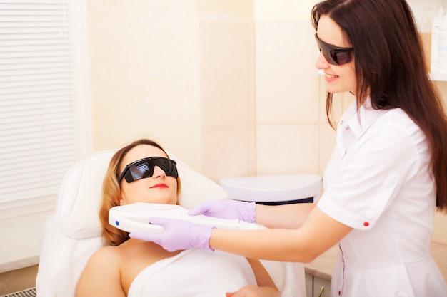 Donna che fa depilazione laser nello studio di bellezza