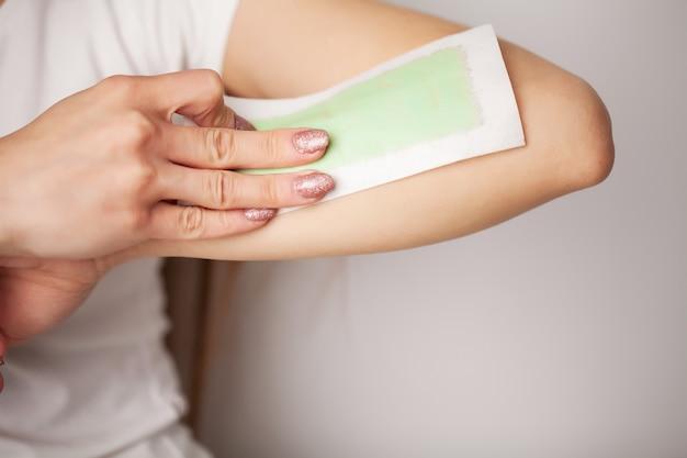 Donna che fa depilazione sulle loro mani a casa nel bagno