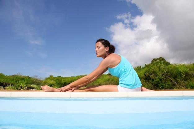 Donna che fa esercizi di stretching in piscina