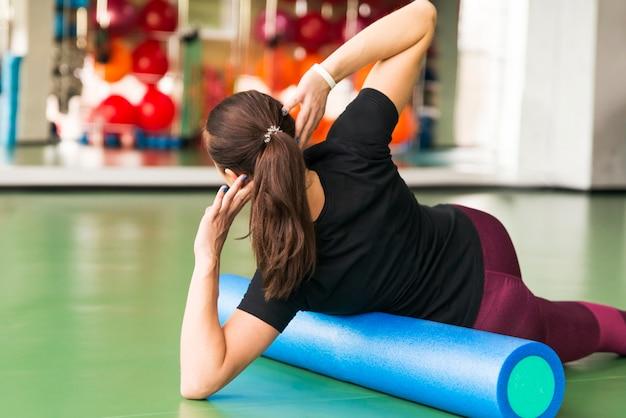 Donna che fa esercizio del rullo di schiuma su un pavimento in palestra
