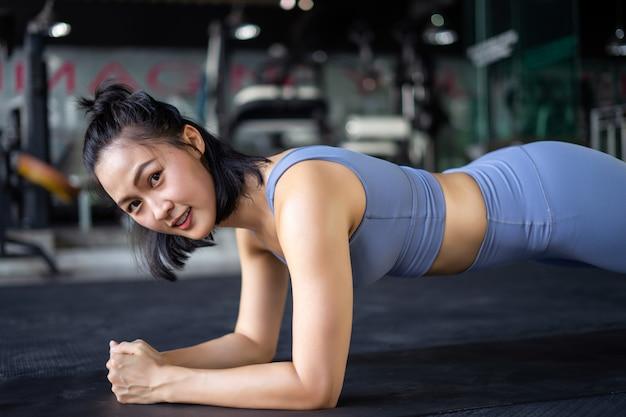 Donna che fa esercizio della plancia sul tappeto in palestra.