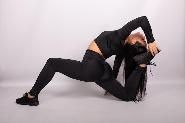 Donna che fa esercizio di gamba per allungare i muscoli. sport e fitness donna, yoga