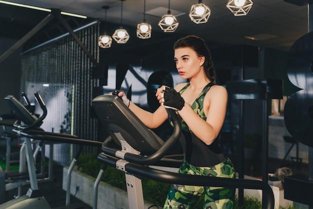 Donna che fa esercizio di gambe sulla macchina stepper scale, nel centro fitness palestra. uno stile di vita sano. concetto di fitness.