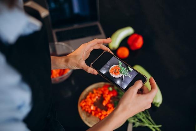 Donna che fa foto di un pasto sul suo telefono