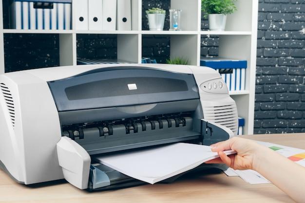 Donna che fa fotocopia facendo uso della copiatrice nell'ufficio