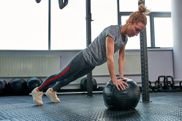 Donna che fa gli esercizi con fitball nella classe della palestra di forma fisica. coinvolgere i muscoli addominali core. concetto di immagine di stile di vita sano per le donne.