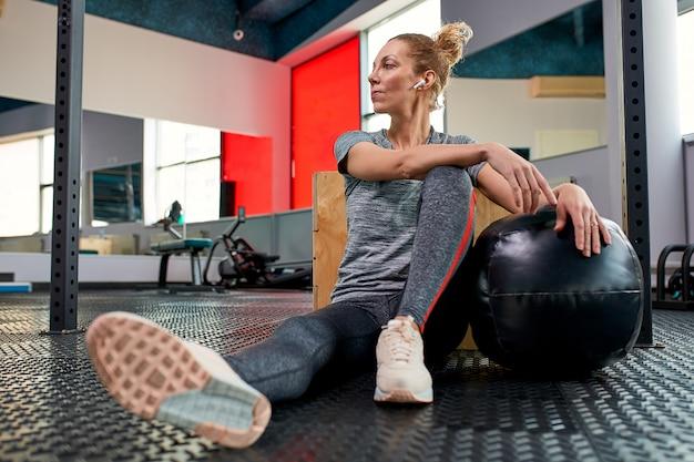 Donna che fa gli esercizi con fitball nella classe della palestra di forma fisica
