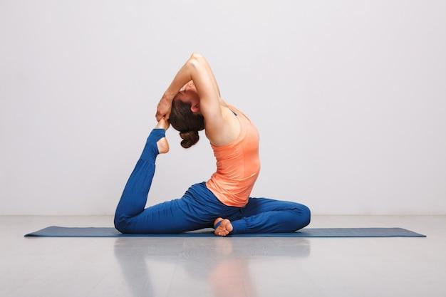 Donna che fa hatha yoga asana eka pada rajakapotasana
