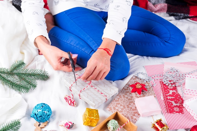 Donna che fa il contenitore di regalo che decora con il nastro