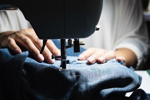 Donna che fa la rappezzatura dei jeans facendo uso della macchina per cucire - concetto di cucito domestico di diy