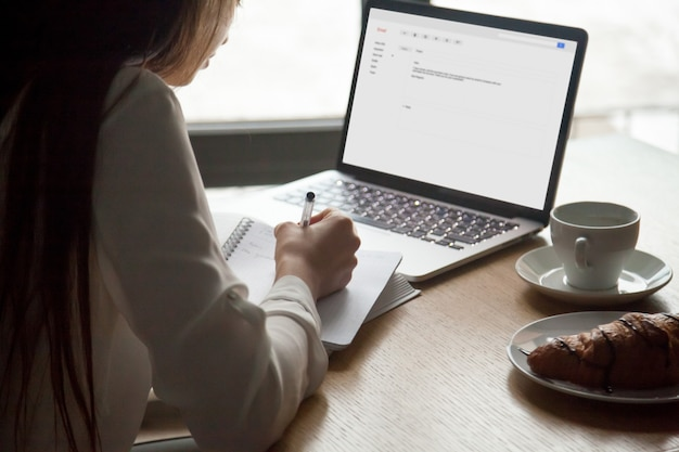 Donna che fa le note che legge la lettera del email sul computer portatile in caffè