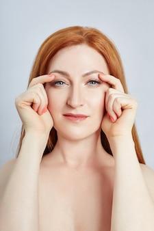 Donna che fa massaggio facciale, ginnastica, linee di massaggio e occhi e naso in plastica. massaggio