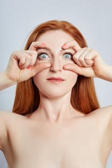 Donna che fa massaggio facciale, ginnastica, linee di massaggio e occhi e naso in plastica