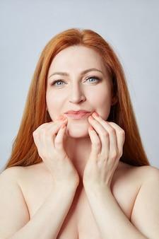 Donna che fa massaggio facciale, linee di massaggio e occhi e naso di plastica della bocca