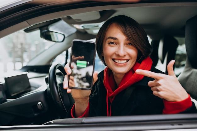 Donna che fa pagare la sua automobile e che esamina il cherger sul telefono del bher
