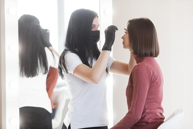 Donna che fa procedura cosmetica del sopracciglio. sopracciglio che modella il servizio al suo cliente femminile.