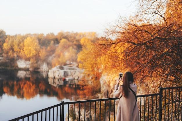 Donna che fa selfie nel parco di autunno