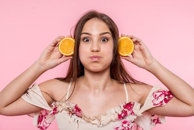 Donna che fa smorfie e si diverte con fette d'arancia