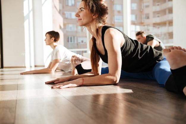 Donna che fa spago e che allunga nel gruppo allo studio di yoga