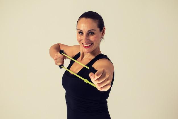 Donna che fa spalla e schiena con fascia elastica fitness
