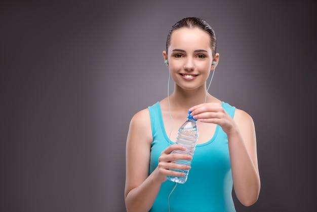 Donna che fa sport con bottiglia di acqua fresca