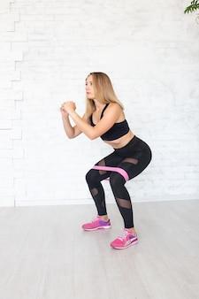 Donna che fa squat con elastico