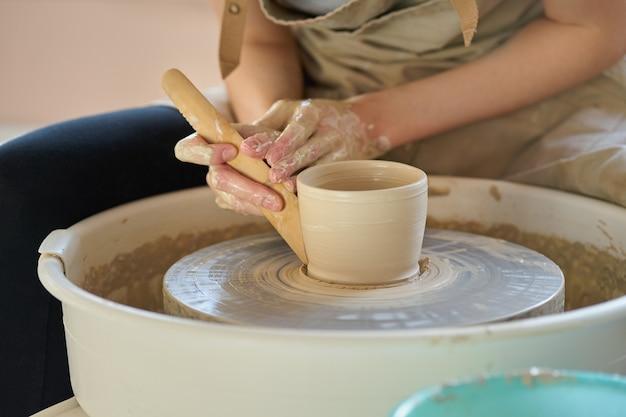 Donna che fa terraglie ceramiche sulla ruota, primo piano delle mani, fuoco sui vasai, palme con terraglie