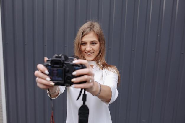Donna che fa una foto di se stessa con una fotocamera reflex e sorridente