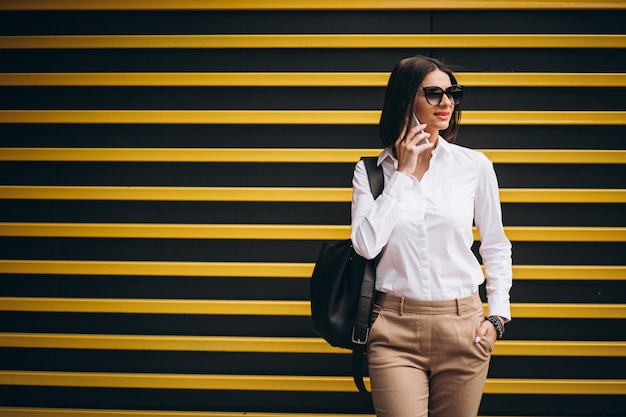 Donna che fa una pausa la parete gialla e che parla sul telefono