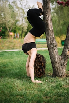 Donna che fa verticale vicino all'albero in parco
