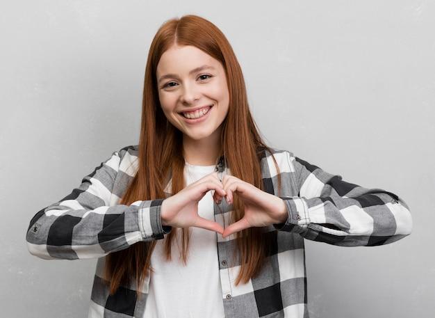 Donna che fa vista frontale di gesto del cuore