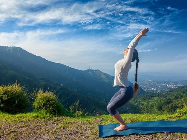 Donna che fa yoga asana utkatasana all'aperto