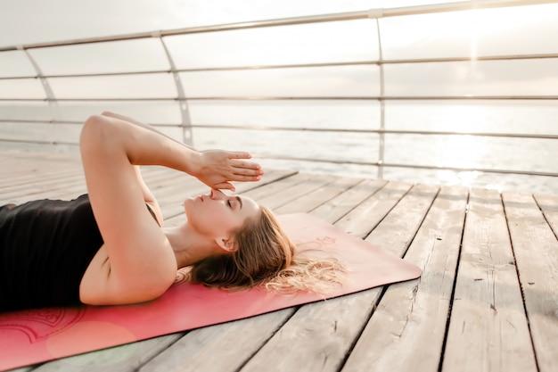 Donna che fa yoga e che medita su spiaggia