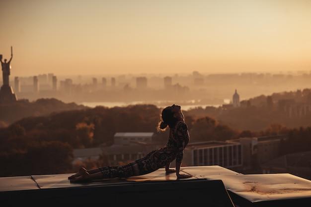 Donna che fa yoga sul tetto di un grattacielo in grande città.