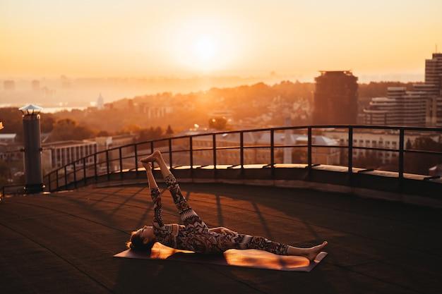 Donna che fa yoga sul tetto di un grattacielo in grande città