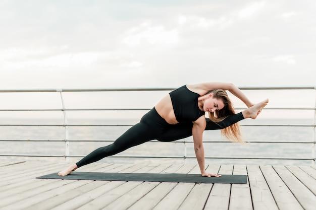 Donna che fa yoga sulla spiaggia e che flette nella posizione di asana difficile