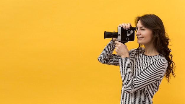 Donna che filma con una retro macchina fotografica