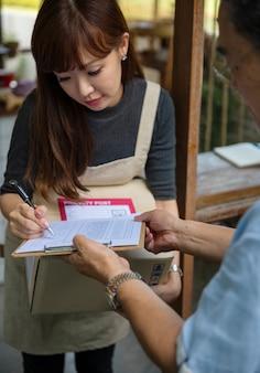 Donna che firma per un pacchetto di consegna
