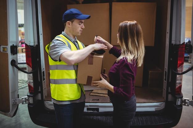 Donna che firma sul dispositivo al pacco di consegna in furgone