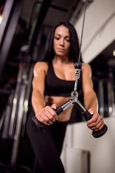 Donna che flette i muscoli sulla macchina del cavo in palestra