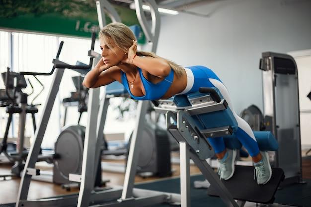 Donna che flette la schiena e i muscoli addominali sul banco